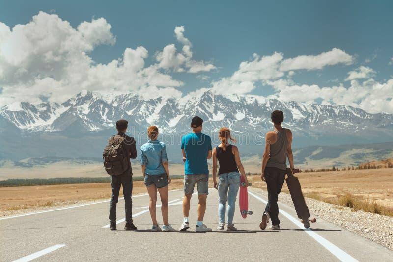 Soportes de los viajeros del grupo de los amigos en el camino recto contra las montañas imágenes de archivo libres de regalías