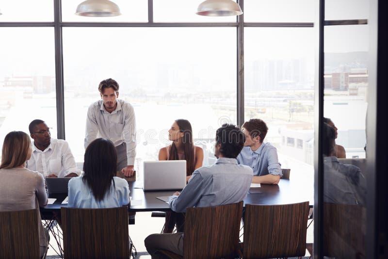 Soportes del hombre joven que se dirigen al equipo en una reunión en una sala de reunión fotografía de archivo libre de regalías