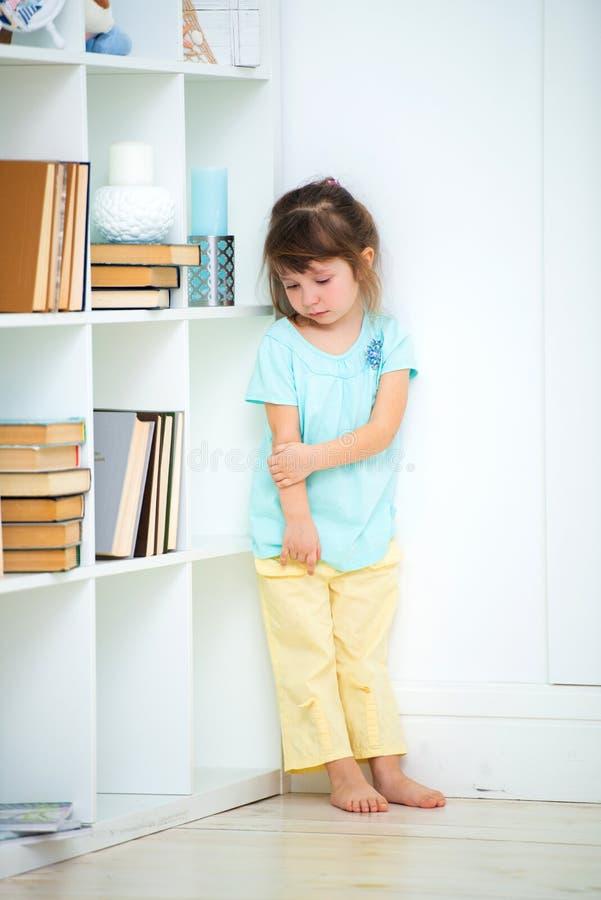 Soportes delincuentes tristes pequeños de una muchacha castigados en la esquina Vinos y castigo de niños imagen de archivo