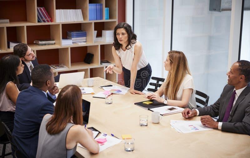 Soportes femeninos del encargado que se dirigen al equipo en la reunión de la sala de reunión foto de archivo