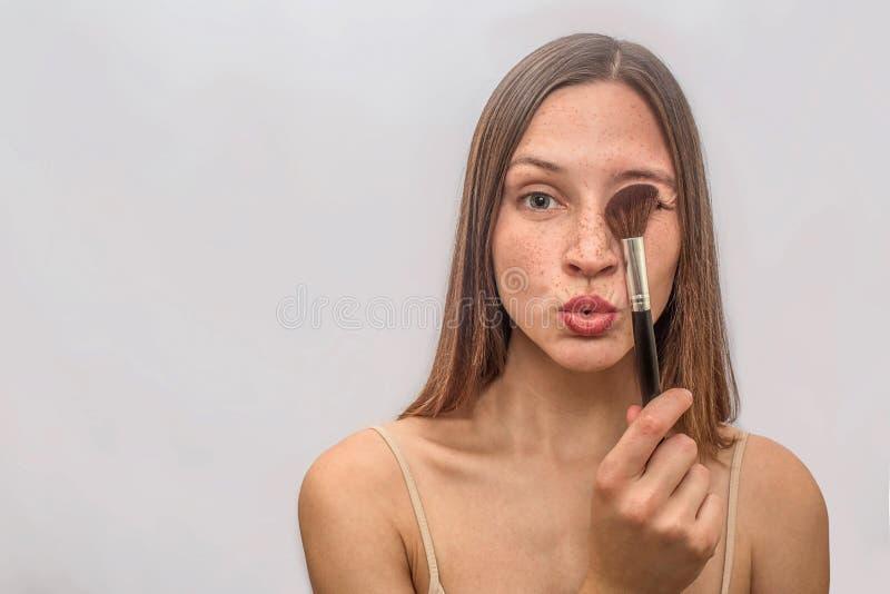 Soportes pecosos y actitudes de la mujer joven Ella coveres un ojo con el cepillo Ella sostiene los labios juntos Aislado en gris imagen de archivo libre de regalías