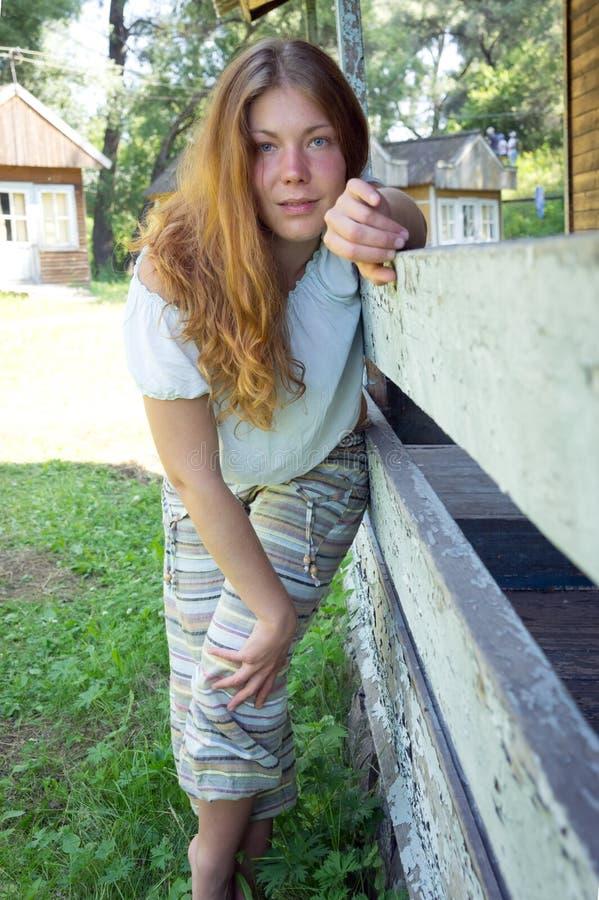Soportes pelirrojos de la muchacha, inclinándose en una verja de madera, en el verano en un día soleado fotos de archivo libres de regalías