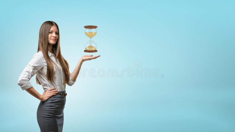 Soportes rubios y controles de una empresaria una palma de la mano para arriba con un reloj de arena grande que asoma sobre él foto de archivo libre de regalías