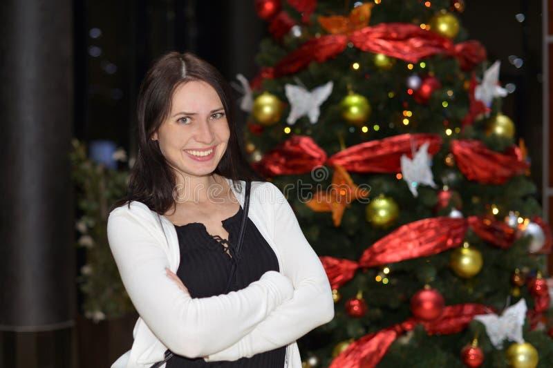 Soportes sonrientes de una mujer joven cerca del árbol de navidad fotografía de archivo