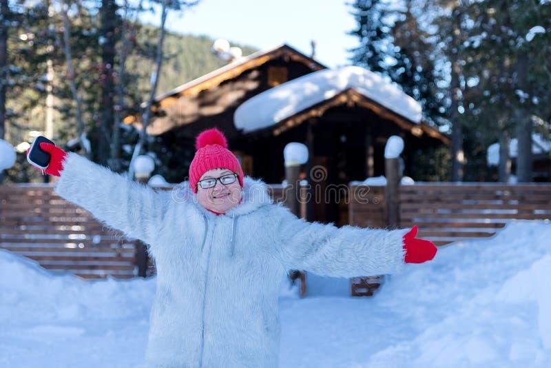 Soportes y sonrisas alegres de la mujer feliz delante de una casa de madera rústica entre las nieves acumulada por la ventisca en fotografía de archivo
