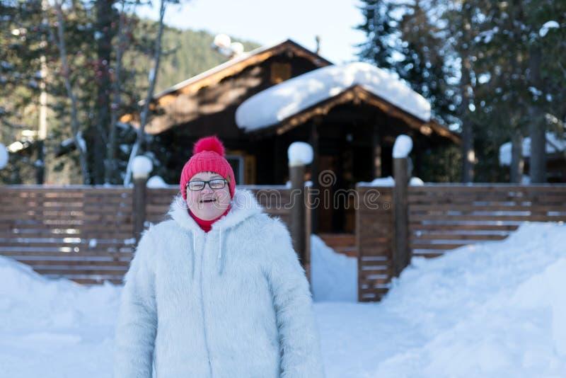 Soportes y sonrisas mayores de la mujer feliz delante de una casa de madera rústica entre las nieves acumulada por la ventisca en foto de archivo