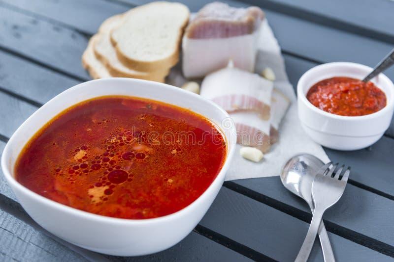 Soppa, en platta av röd ukrainsk borscht med bacon och ketchup på en grå träbakgrund arkivfoton