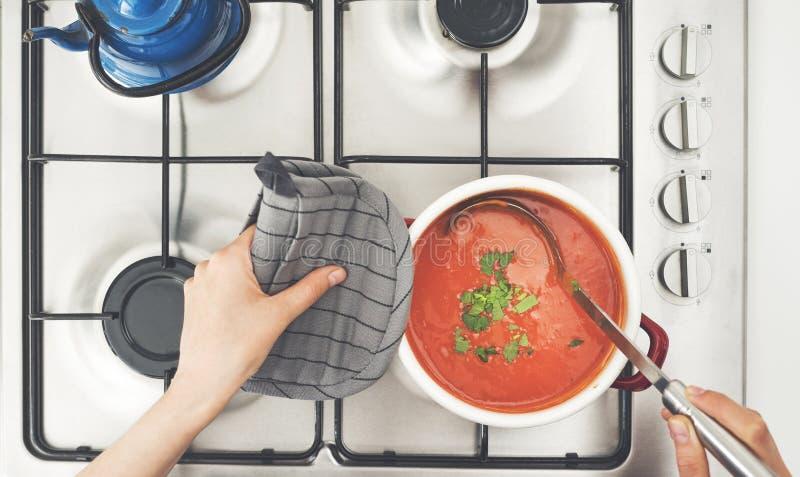 Soppa för kvinnamatlagningtomat på ugnen i kök arkivfoton