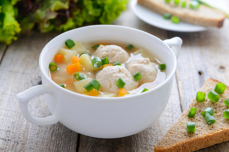 Soppa med köttbullar i den vita bunken fotografering för bildbyråer
