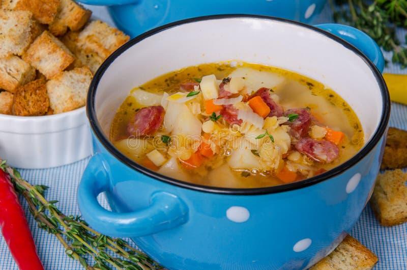 Soppa med linser, grönsaker och korvar royaltyfria foton