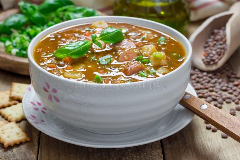 Soppa med linser och korvar arkivbild