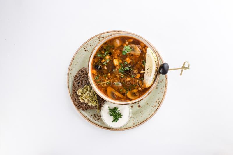 Soppasaltwort med kött, rökte korvar och svarta oliv med gräddfil och rågbröd som isoleras på vit bakgrund royaltyfria bilder