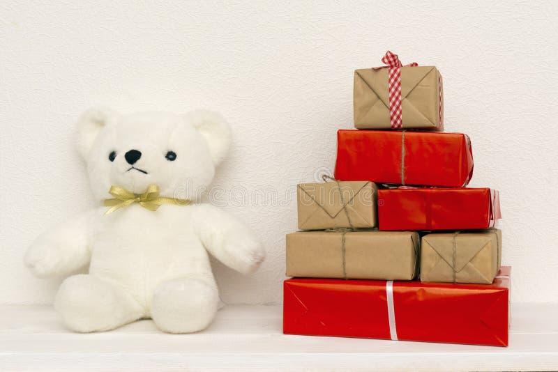 Sopporti la bambola con i contenitori di regalo su fondo bianco fotografie stock libere da diritti