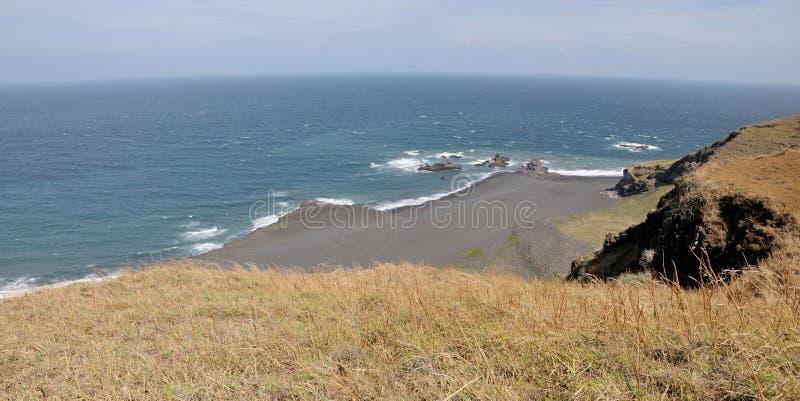 Sopra - een eenzaam zwart zandstrand met woeste golven stock fotografie
