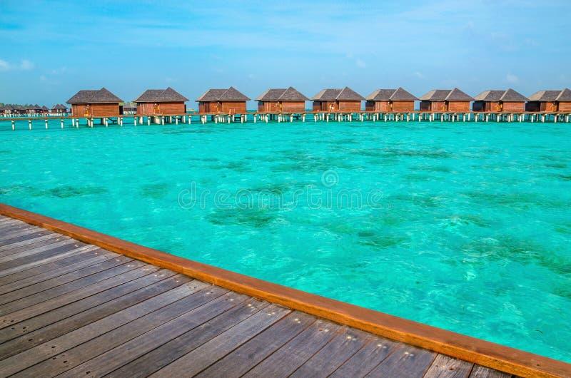 Sopra i bungalow dell'acqua su un'isola tropicale, le Maldive fotografia stock libera da diritti