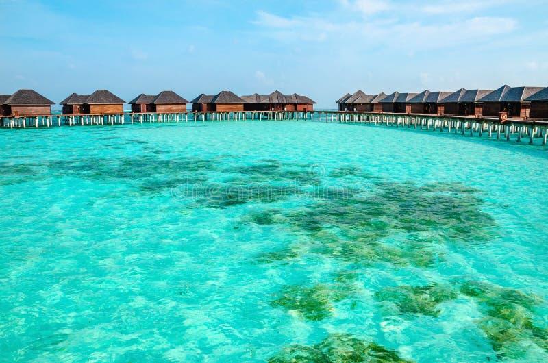 Sopra i bungalow dell'acqua su un'isola tropicale, le Maldive immagini stock libere da diritti