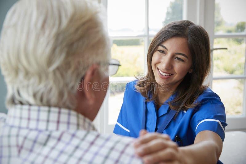 Sopra il punto di vista della spalla dell'infermiere sulla visita domestica con l'uomo senior fotografie stock