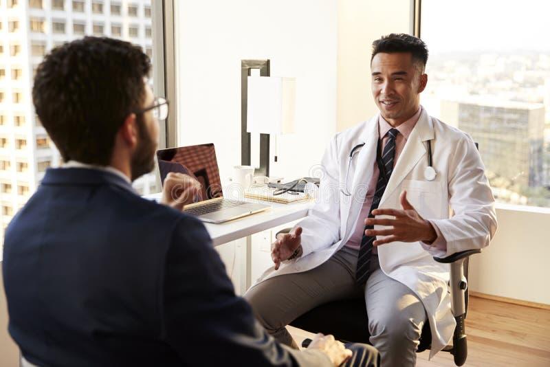 Sopra il punto di vista della spalla dell'uomo che ha consultazione con il dottore maschio In Hospital Office fotografie stock