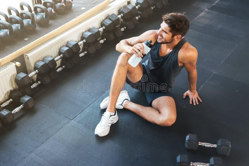 Sopra la foto dell'uomo di forma fisica che si siede nella palestra fotografia stock libera da diritti