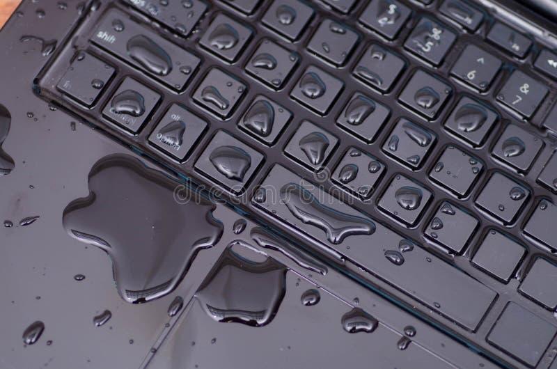 Sopra la vista del computer portatile con danno della goccia di acqua liquido bagni e rovesci sulla tastiera, concetto di inciden fotografia stock libera da diritti