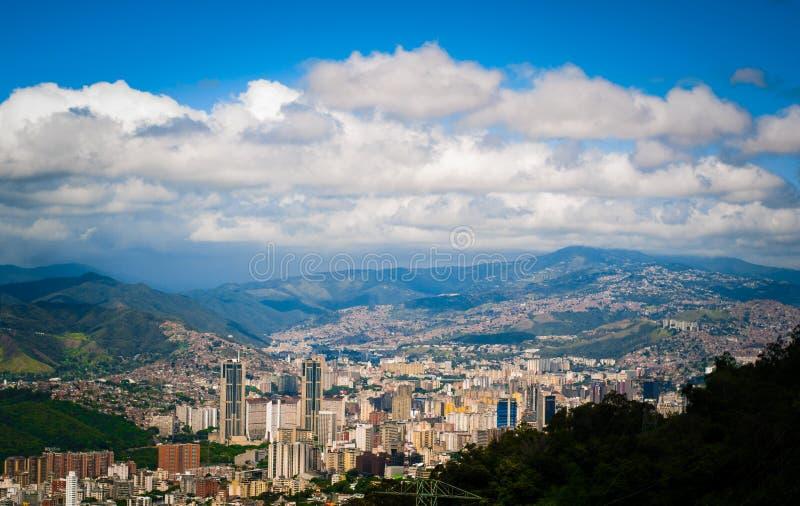 Sopra la vista della città di Caracas nel Venezuela dalla montagna di Avila durante il giorno di estate nuvoloso soleggiato fotografia stock libera da diritti