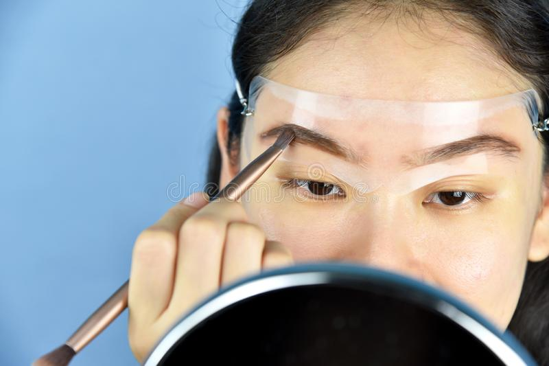 Sopracciglia che modellano il modello di trucco, donne asiatiche che riempiono le sopracciglia per guardare più spesso immagine stock