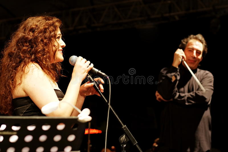 Soprano and conductor. Members of the Maltepe Symphonic Orchestra perform live at Maltepe open air stage on July 11, 2010 in Istanbul. Soprano Selva Erdener with royalty free stock images