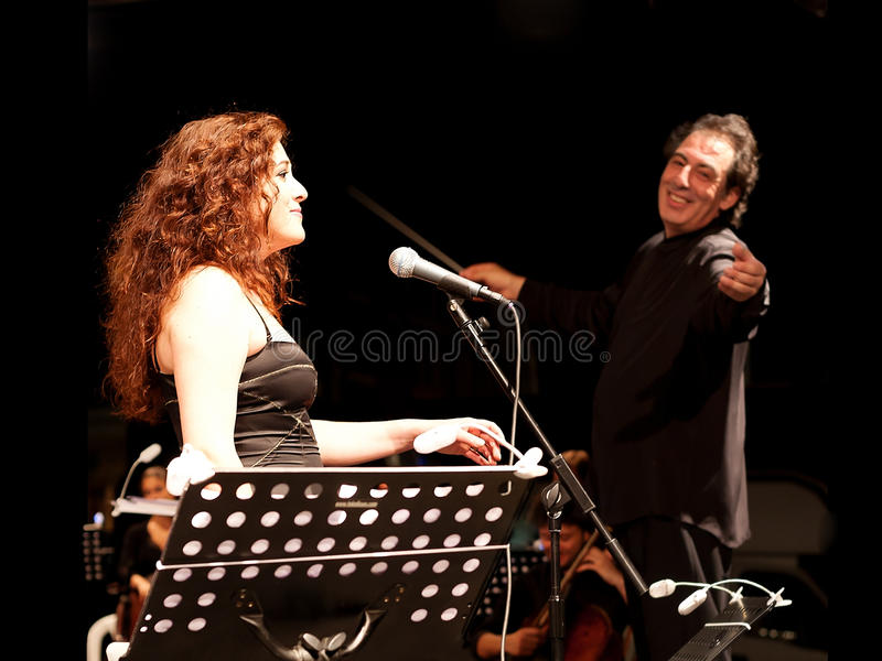 Soprano and Conductor. Members of the Maltepe Symphonic Orchestra perform live at Maltepe open air stage on July 11, 2010 in Istanbul royalty free stock photography