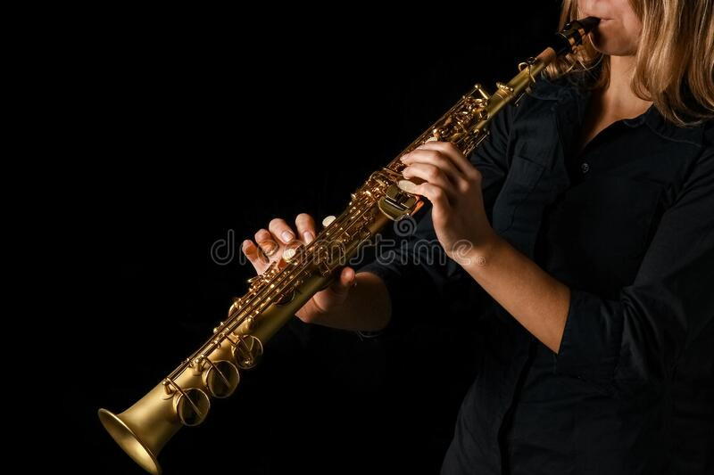Soprano saxophone in hands on a black background stock images