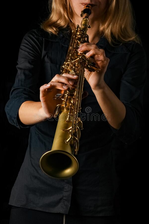 Soprano saxophone in hands on a black background stock photos