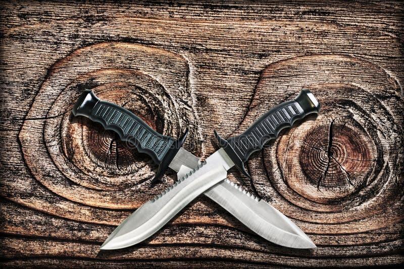 Sopravvivenza tattica Bowie Knives With Crossed Blades di caccia di combattimento di lerciume sul vecchio Pinewood fondo annodato fotografia stock