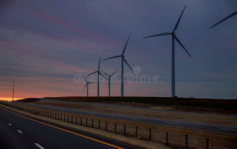 Sopros das energias eólicas nas explorações agrícolas ocidentais da turbina eólica de Texas no por do sol colorido que mostra tra imagem de stock royalty free