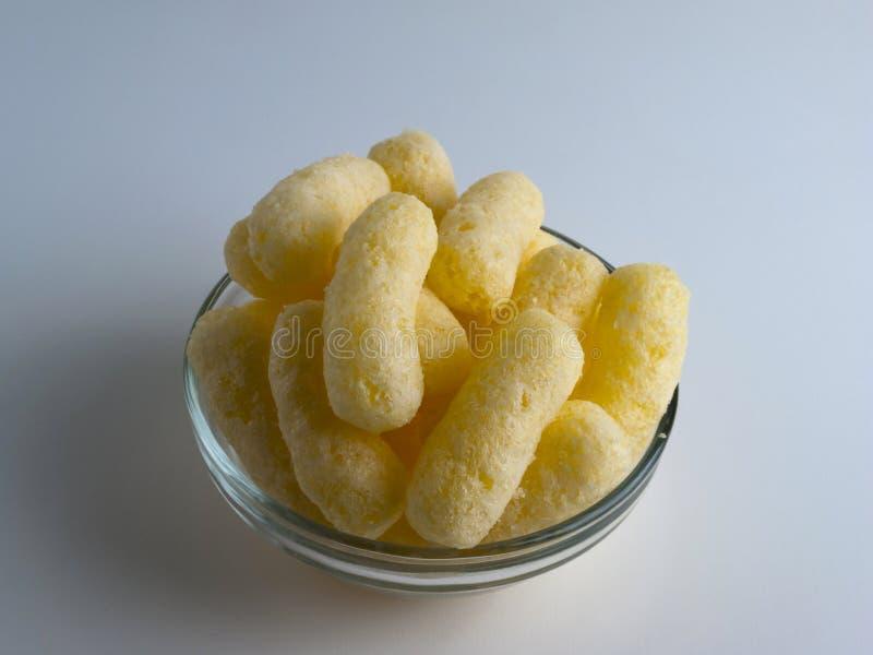 Sopros do milho em uma bacia de vidro Petiscos soprados Flavored crocantes Partido, petiscos do filme imagens de stock