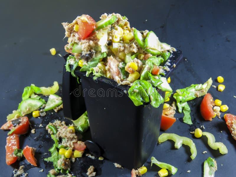 Soptunna som fylls med slösad mat arkivfoto