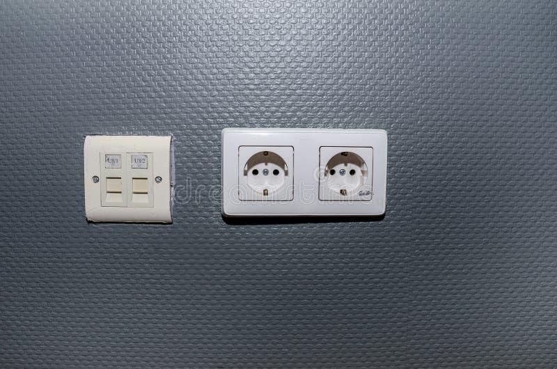 Soquetes em uma parede cinzenta no escritório Peça da parede com soquetes fotografia de stock
