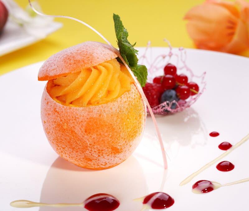 Sorbet eller glass i iskall apelsin dekorerade med mintkaramellbladet och c arkivbilder