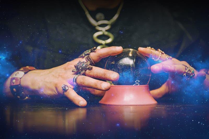 Sorcerer använder en kristallkula för att förutsäga framtiden royaltyfri fotografi