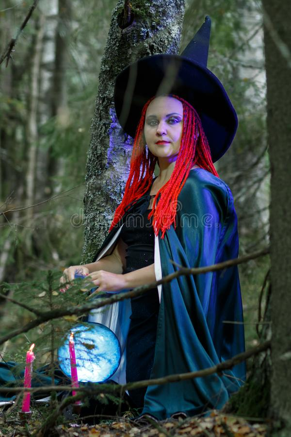 The sorceress in a hat and a black cloak in the forest charms over a luminous crystal ball. Vertical photo royalty free stock image
