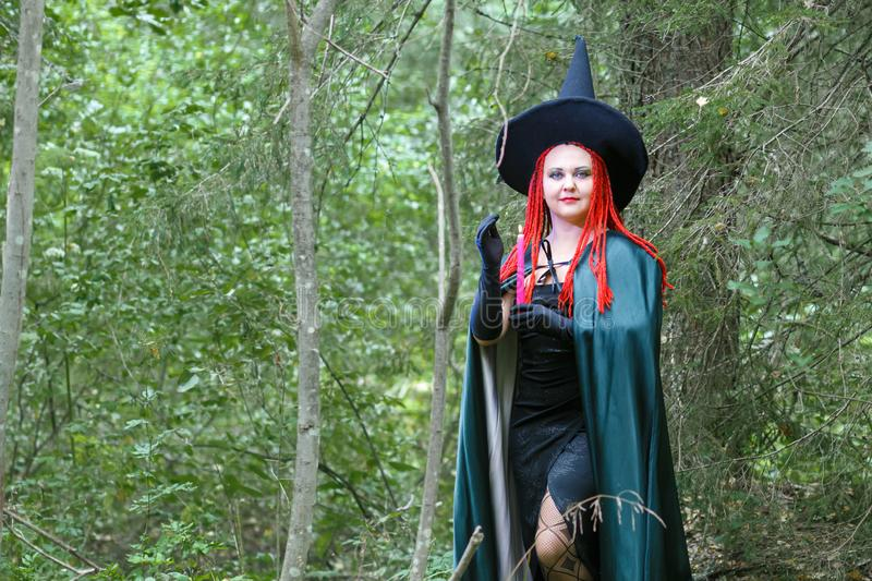 A sorceress with red hair in a pointed hat and a black cloak in the forest is engaged in charms with a candle. Horizontal photo stock photography