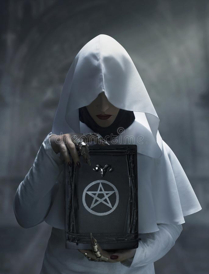 Sorceress holding a spell magic book with pentagram symbol. Sorceress in white hooded cloak holding a spell magic book with pentagram symbol standing in the royalty free stock photos
