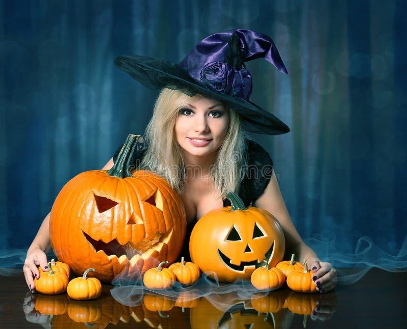 Sorcière avec des potirons de Halloween Beau blond heureux photographie stock