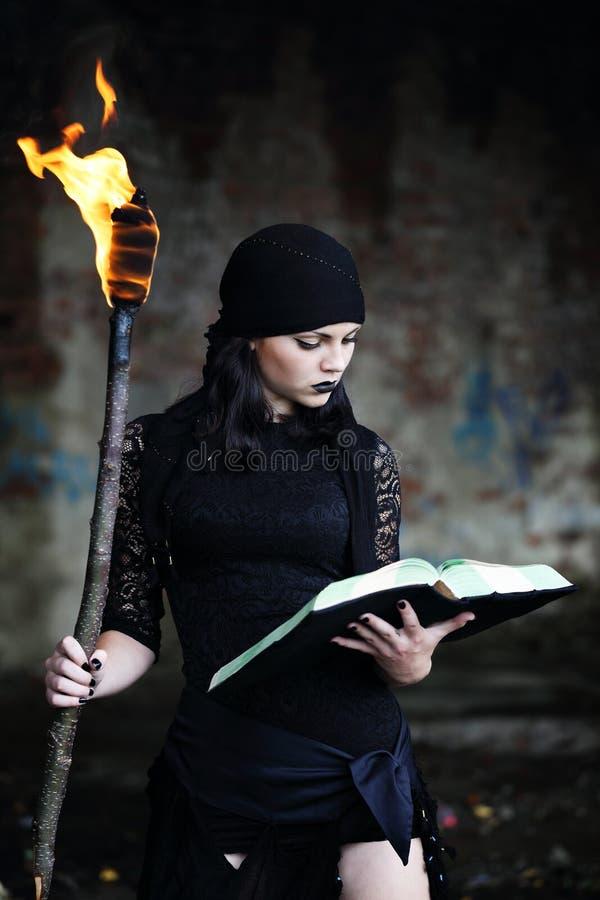 Sorcière avec un livre images libres de droits