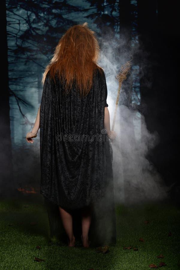 Sorcière entrant dans la forêt tenant sa baguette magique avec le brouillard photographie stock