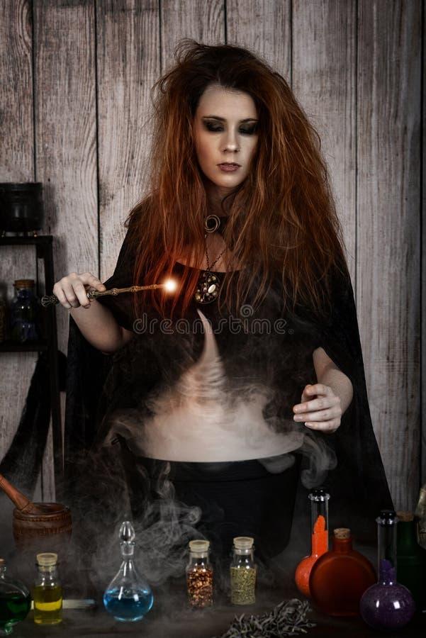 Sorcière jetant un sort magique dans son breuvage magique de chaudron photographie stock