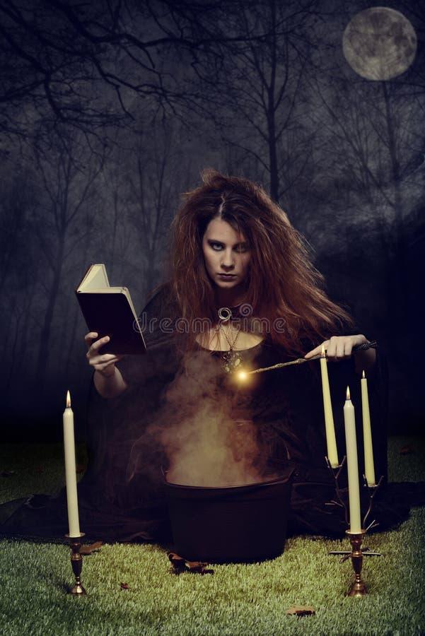 Sorcière la nuit utilisant la magie avec la baguette magique photos stock