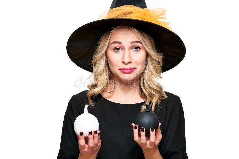 Sorcière magnifique de Halloween essayant de supprimer le rire tout en tenant les potirons minuscules Femme effrontée dans le cha image stock