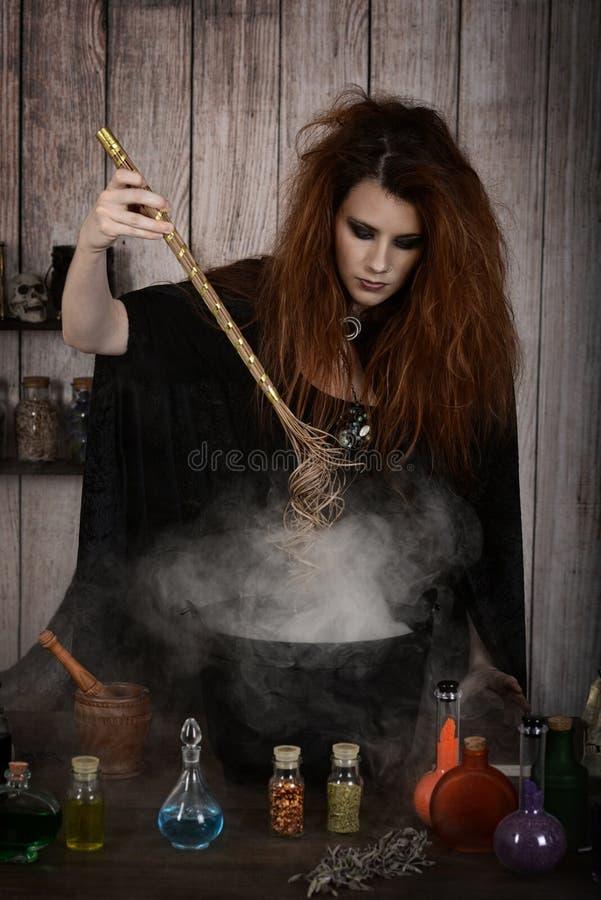 Sorcière remuant son breuvage magique magique avec sa baguette magique image stock