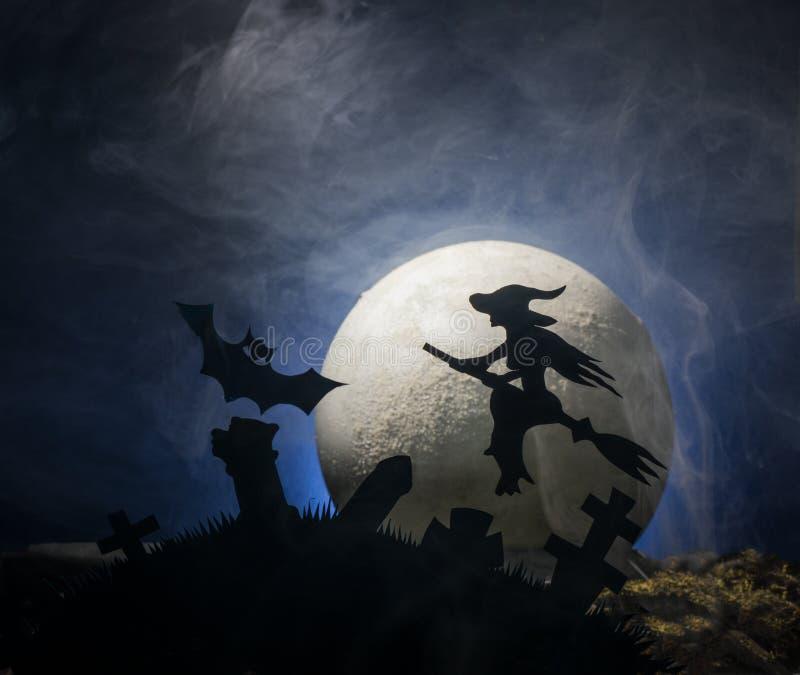 Sorcière sur un manche à balai dans la perspective de la lune, Halloween images stock