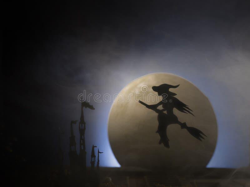 Sorcière sur un manche à balai dans la perspective de la lune, Halloween photo stock