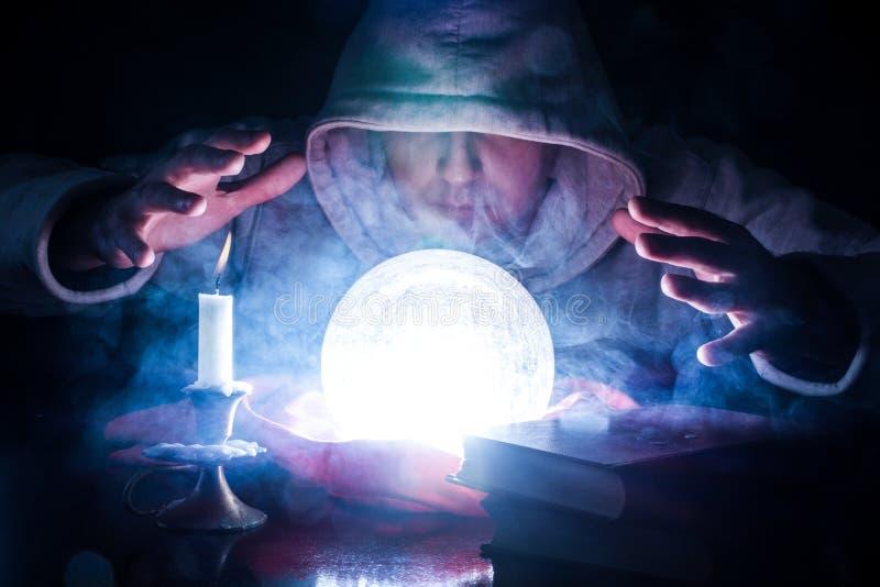 Sorcier qui prévoit le destin avec la boule magique rougeoyante photos libres de droits
